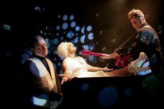 Vanhan naisen vierailu esityskuva, kuvassa Claire loikoilee ammeessa, hovimestari myhäilee vierellä, muusikko osoittaa Clairea kitarallaan