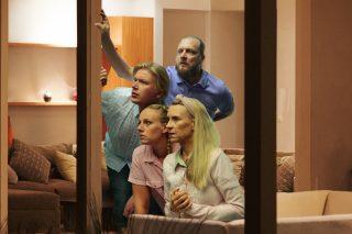 Merenrannalla asuva perhe katsoo ulos ikkunasta.