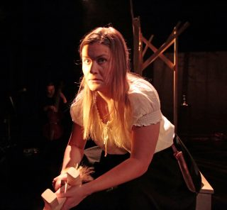 Niskavuoren Loviisa ja Heta esityskuva. Malviina istuu mietteliäänä, muusikko soittaa taustalla pimennossa viola de gambaa