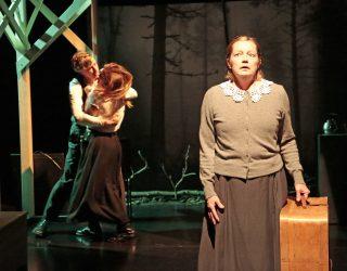 Niskavuoren Loviisa ja Heta esityskuva Juhani ja Malviina suutelevat taustalla, Heta seisoo matkalaukku kädessään
