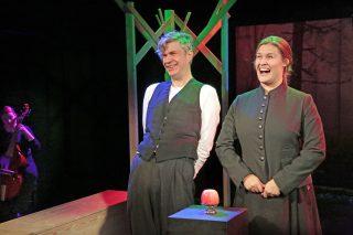 Niskavuoren Loviisa ja Heta esityskuva. Juhani ja Loviisa naureskelevat ottaessaan vieraita vastaan. Muusikko soittaa sivummalla viola de gambaa