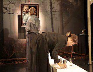 Niskavuoren Loviisa ja Heta esityskuva. Loviisa katsoo peiliin, Heta asettelee päydän astioita