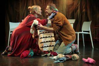 Perheen äiti ja isä hassuttelevat, värikkäitä villasukkia lojuu lattialla.