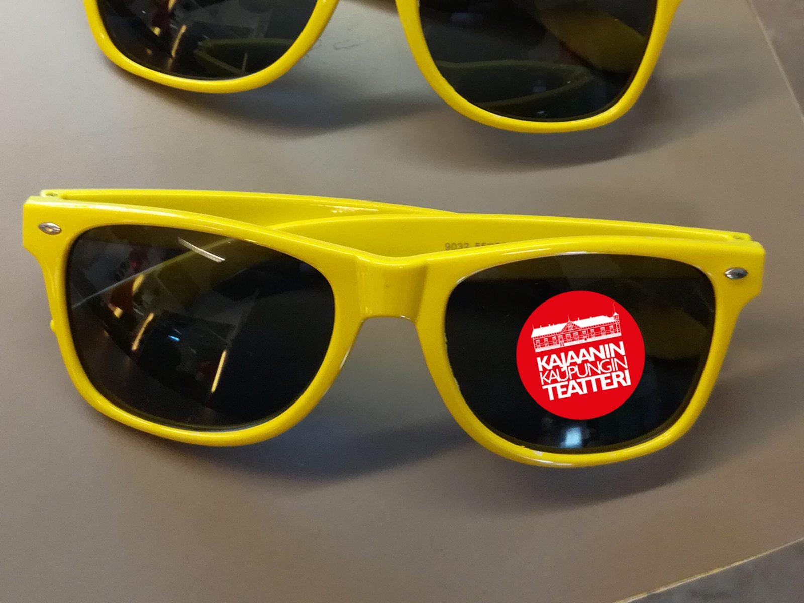 Keltaiset aurinkolasit joissa teatterin logotarra