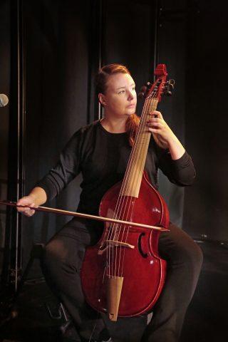 Niskavuoren Loviisa ja Heta esityskuva, äänisuunnittelija/muusikko soittaa viola de gambaa