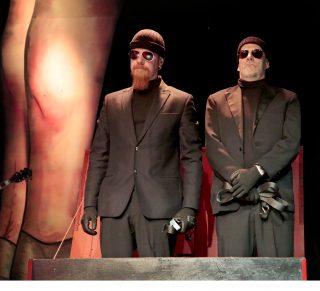 Vanhan naisen vierailu esityskuva, Clairen eunukit Toby ja Loby seisovat vierekkäin mustissa puvuissa ja aurinkolaseissa