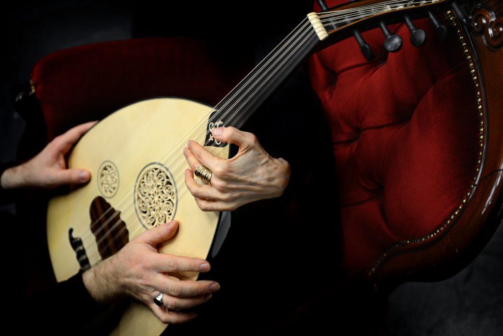 Autuas elämän arpa. Naisen ja miehen käsi arabialaisen oud-soittimen kannella