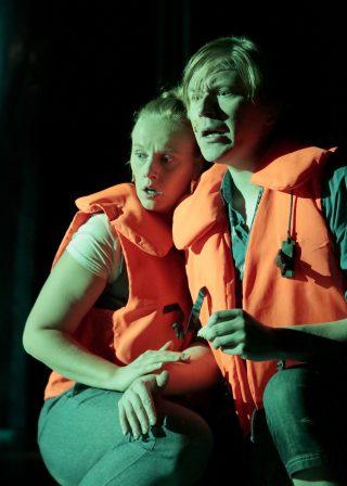 Hylje esityskuva. Tyttö ja poika pelastusliiveissä tukeutuvat toisiinsa
