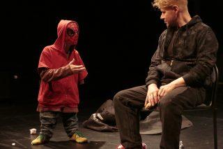 Esityskuva. Pienempi mies Spiderman - asussa selittää tuolilla istuvalle miehelle