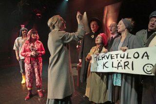 Vanhan naisen vierailu - esityskuva, opettajatar (Satu Turunen) johtaa Clairen vastaanottojuhlan kuoroa asemalla.