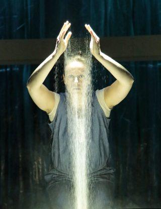 Hylje esityskuva, Näyttelijä Salla Loper valuttaa käsistään hiekkaa kasvojensa edessä