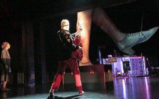 Vanhan naisen vierailu esityskuva, muusikko Jari Rättyä osoittaa kitaralla näyttämön katosta laskeutuvaa valtavaa jalkaa
