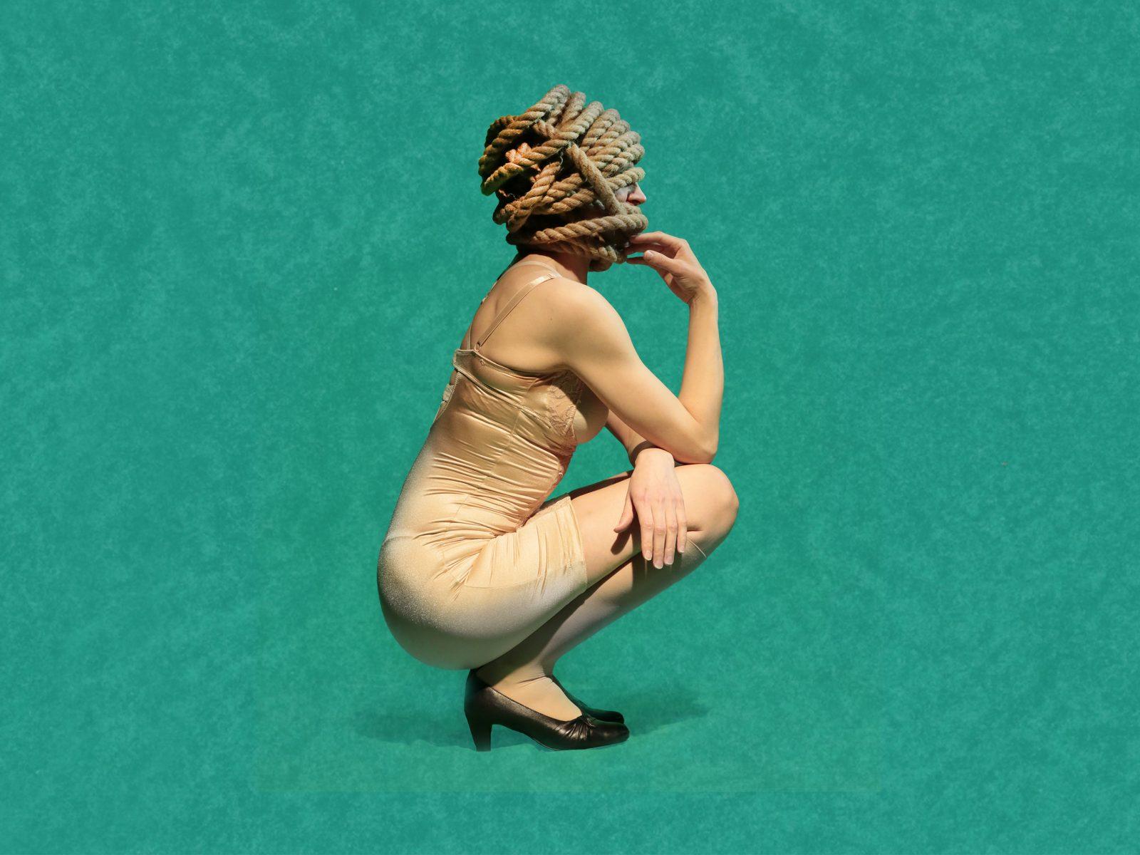 Medusan huone -näytelmän mainoskuva. Alushameeseen pukeutunut nainen istuu sivuttain kyykyssä päässään manillaköydestä muotoiltu kampaus.